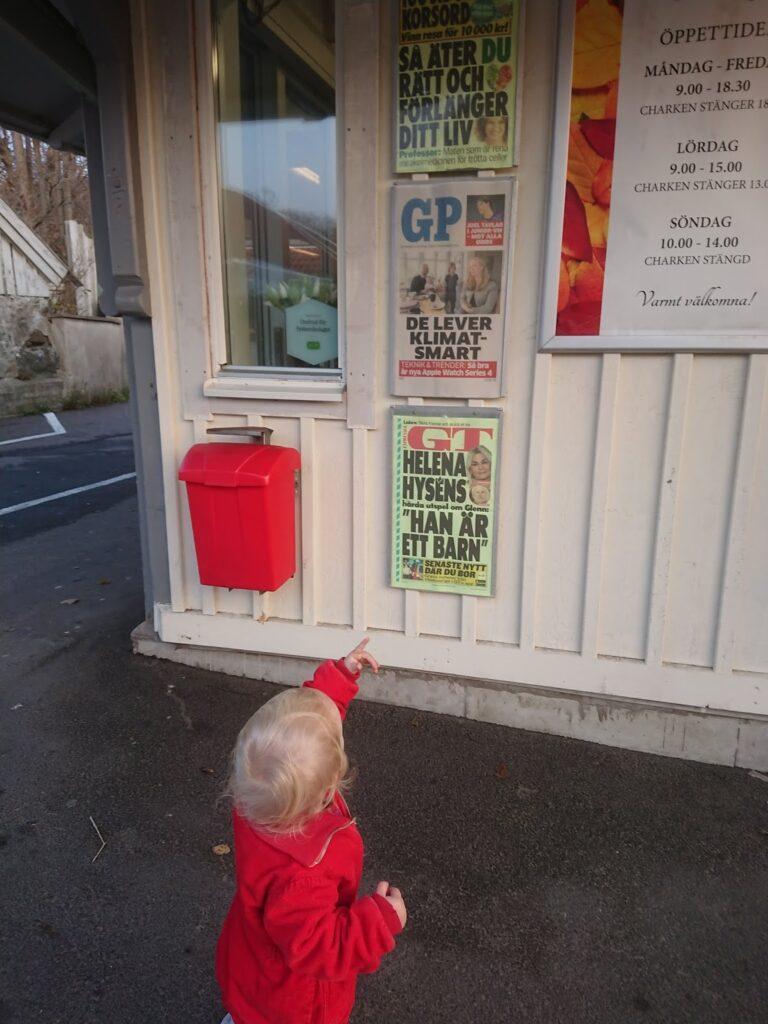 Lilla Eila tittar på en löpsedel med sin familj på