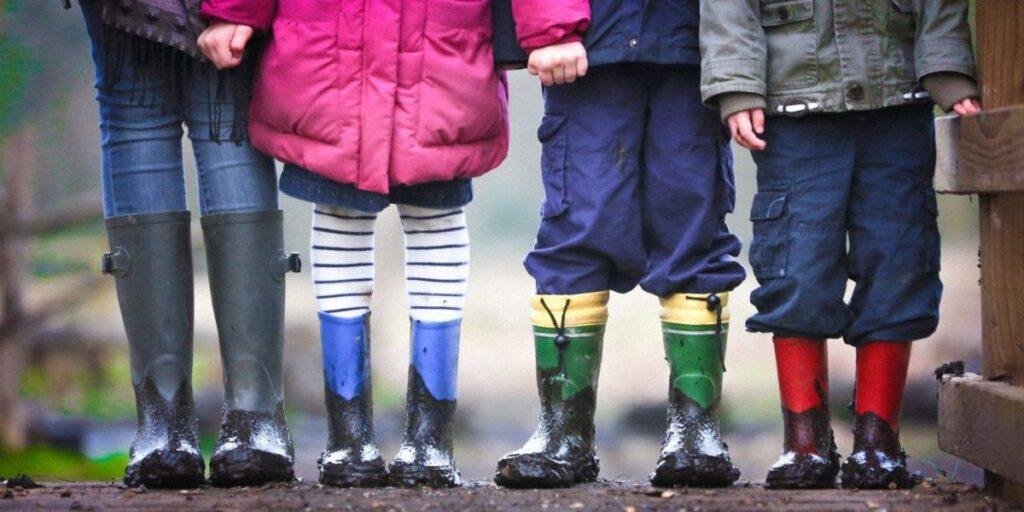 Foto på barnfötter med leriga gummistövlar