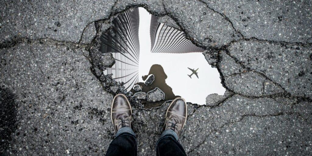 Foto på ett hål i asfalt där ett flygplan syns speglat i en vattenpöl